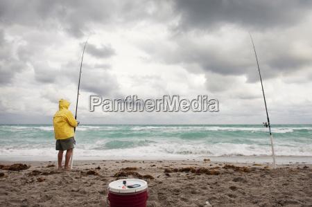 homemsegurandocana de pescaenquantoficarligadopraiacontraceu nublado